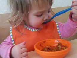 kindje-eet-warm-uit-bakje-met-oranje-slab
